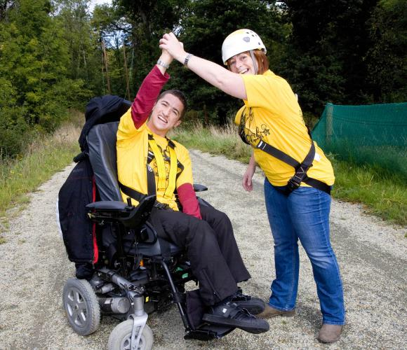 Young man using a powered wheelchair celebrates with young woman after completing a zip lining event