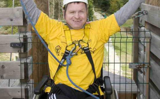 Adult wheelchair user with arms in the air after completing a zip line