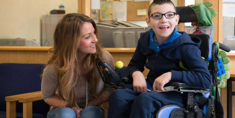 A mother and her son, who is a wheelchair user, wait at the reception