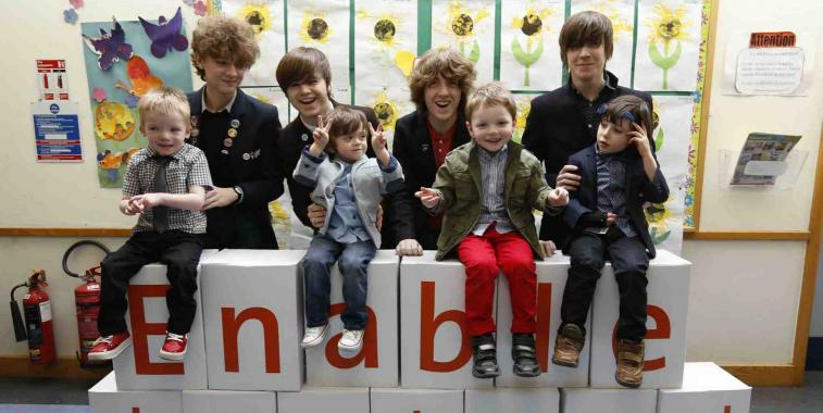 Four members of the rock group the Strypes stand behind four children sitting on boxes