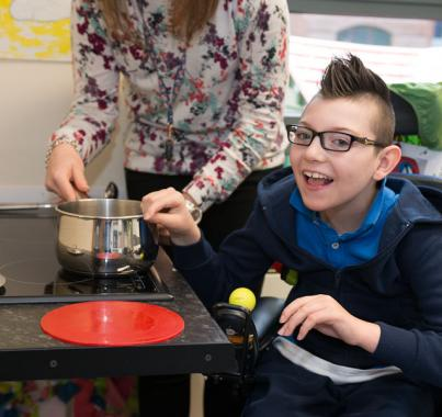 Young boy using wheelchair cooking with a pot at adapted kitchen