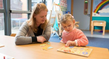 Young girl makes a jigsaw puzzle with Montessori teacher